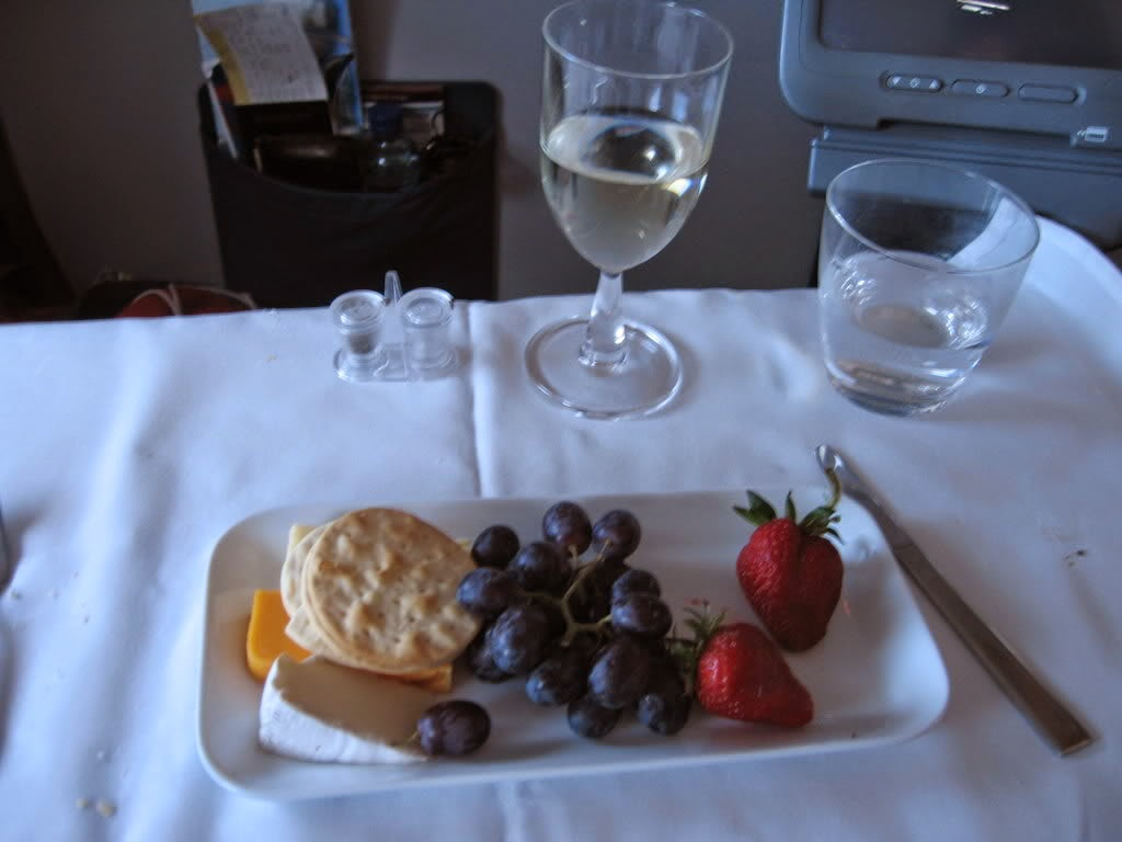 Cheese and Fruit Snack or Dessert on white plate with wine glass of water on white table cloth