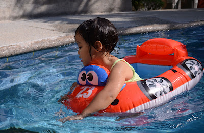 Kecil driving her float in the pool