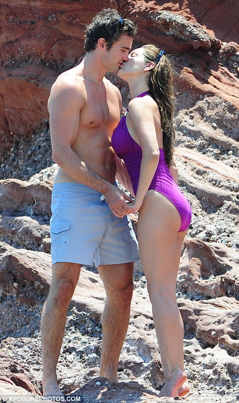 Purple patch: Beach babe Kelly Brook back on smiling form as she smooches on sand in mauve cossie with beau Thom Evans