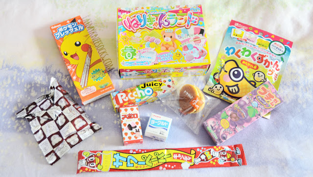 The contents of the June 2015 Japan Candy Box from Blippo: Kabuya fish gummies, Popin' Cookin' DIY candy, Pokemon pocky biscuit sticks, Meiji bubblegum, Puccho chewy candy, Marukawa Fusen bubblegum, Yaokin sour paper candy, dorayaki, Meiji Kotsubu chocolates, and Lotte Koala's March biscuits.