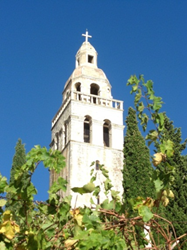 Stone Croatian church against blue sky with green foliage