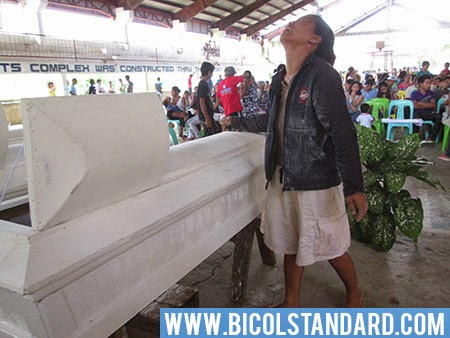 The wife of one of the victims of the Caramoan massacre bawls hysterically before the coffin of her husband.
