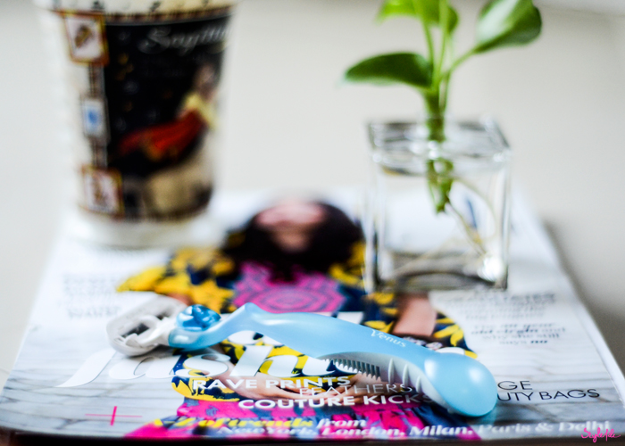 The Gillette Venus ladies razor, placed on a background of ELLE magazine with a mug and planter, is the perfect tool for shaving as it is economical and ergonomically designed