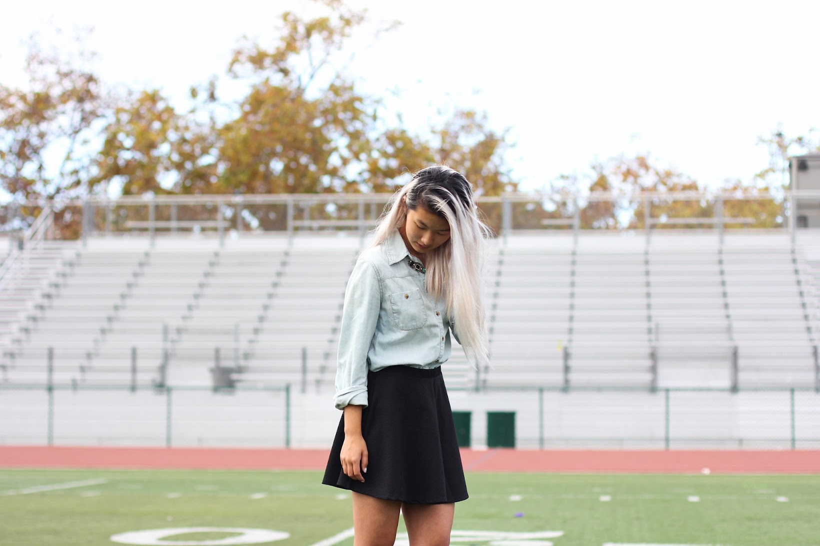 A fall outfit composed in front of some bleachers.