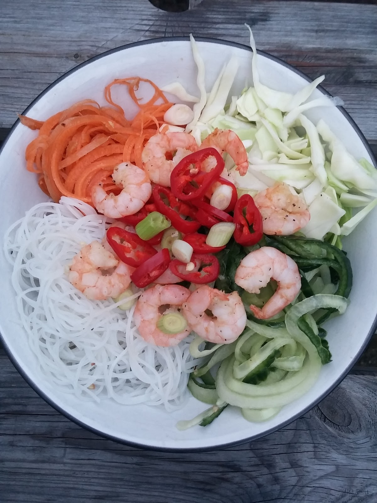 Colourful vietnamese salad of carrots, raw white cabbage, cucumber, rice noodles, king prawns and chilli