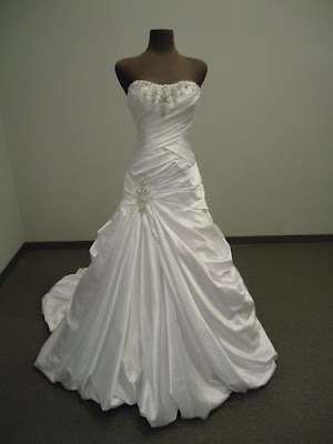 A-Line strapless wedding gown with criss-cross torso, ruffle style and embroidery.