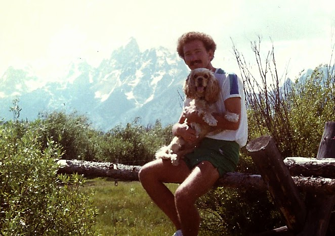 Barry and his cocker spaniel, named Amie, sitting on a rustic wooden fence in front of the Grand Tetons mountain range.