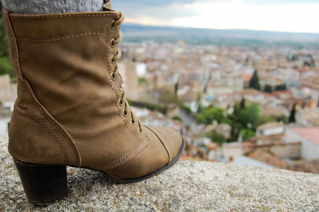 Close up of heeled combat boots on a ledge over looking Granada, Spain.