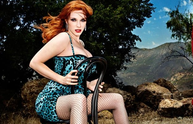 Christina Hendricks in blue animal print outfit sitting on a black chair