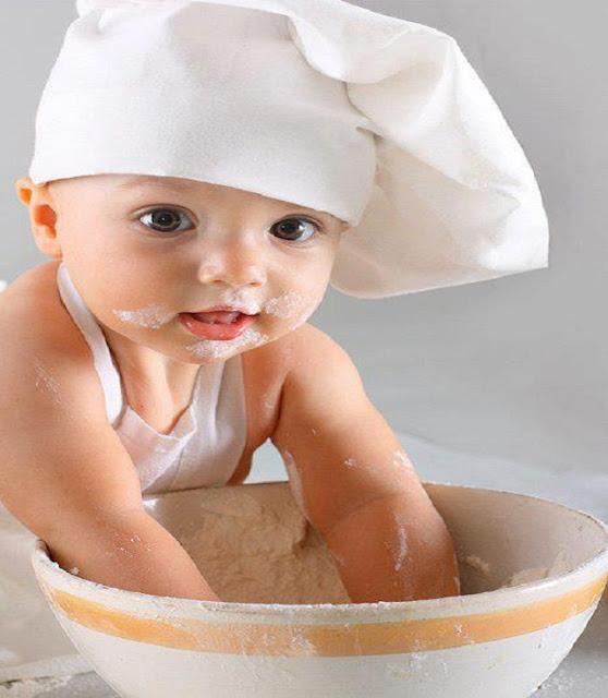 un joli bébé qui joue avec la farine