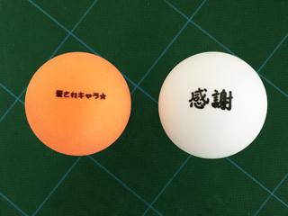 メッセージを印刷したオレンジ色と白のピンポン玉
