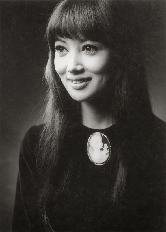 黒い服にブローチをつけてにっこり微笑む浅丘ルリ子