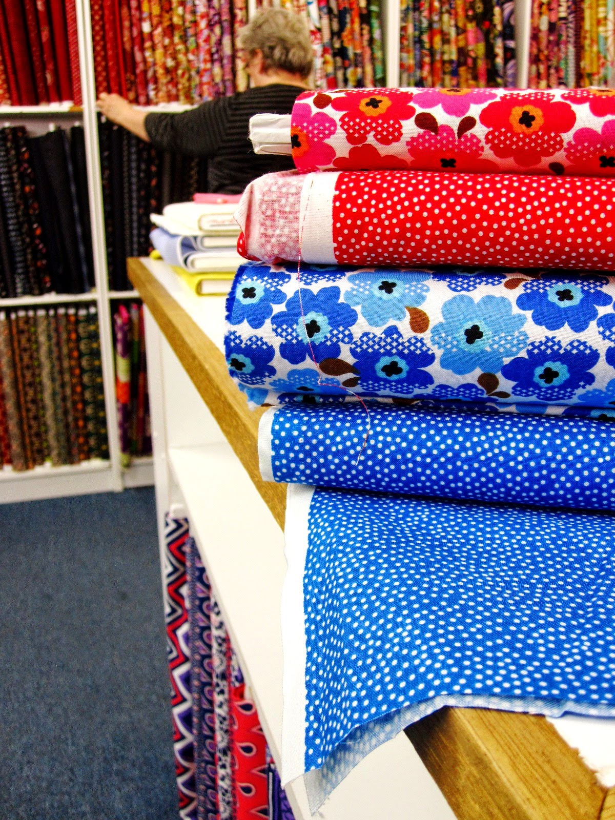 Inside a quilting fabric shop, showing a pile of fabric with Marimekko-like mini prints in the foreground and someone choosing fabric from the shelf in the background.
