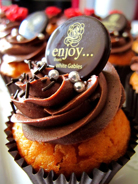 chocolate cupcake with the Enjoy sign on top