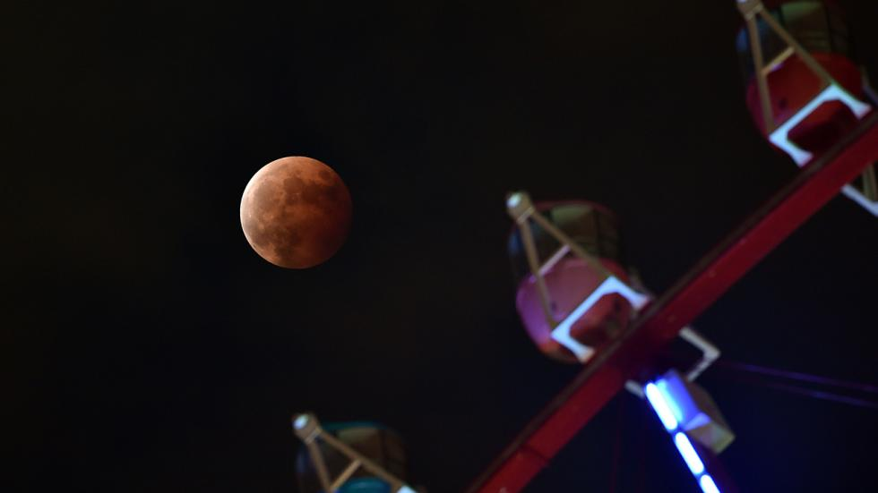 Полное лунное затмение на фоне колеса обозрения в Токио