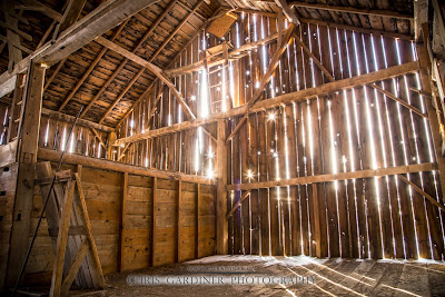 An interior view of a rustic old barn as the setting sun shines in through the cracks in the barn board captured by Chris Gardiner Photography www.cgardiner.ca