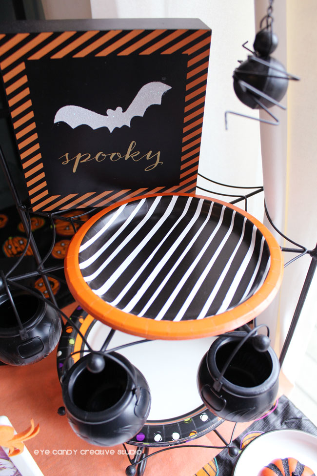 spooky wood sign, spider plate stand, cauldron, paper plates, party