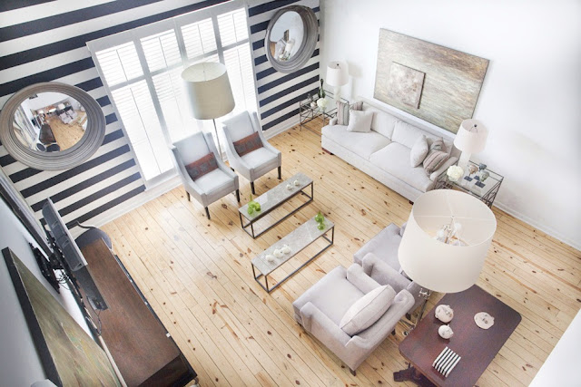 bird's eye view of a living room with knotty wood floors, striped black and white wall with two accent windows, white sofa with matching armchairs and glass coffee tables