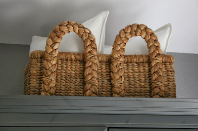 pottery barn seagrass basket with white pillows