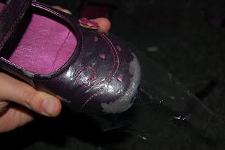 Az egyik pár cipő kézbe véve. A cipő orrára rá van húzva egy nájlonzacskó.