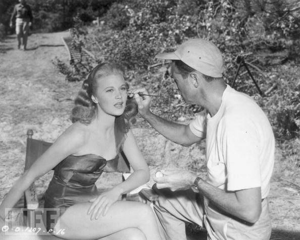 Joan caulfield in a bathing suit having makeup applied by a lucky guy in The Petty Girl movieloversreviews.blogspot.com