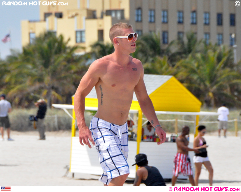 Blonde guy with white sunglasses walking on South Beach in Miami