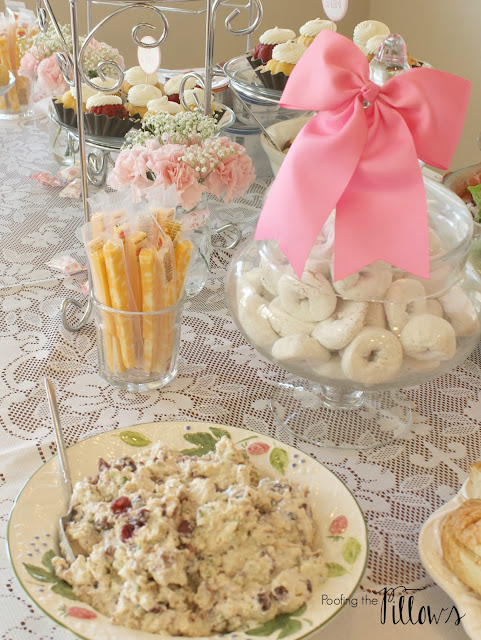 Chicken salad croissants, fruit salad, Caesar salad, Bundtinis, yogurt, and other goodies served at a baby girl shower.