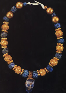 A necklace of Etruscan gold and Phoenician glass beads. These well-made granulated and filigree gold beads represent the pinnacle of technical excellence for ancient goldsmiths. This necklace was probably created in the early sixth century when the Phoenicians and Etruscans were political allies, living and trading in relative harmony Pendant: length, 3.1 cm. British Museum, London