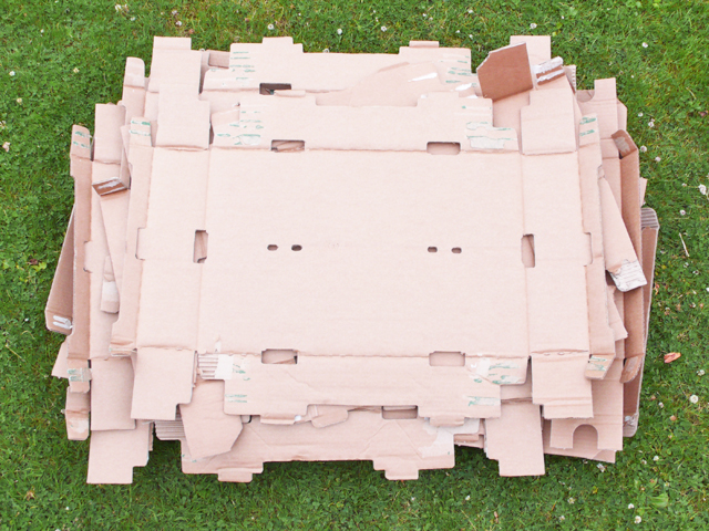 A stack of flattened cardboard boxes viewed from above on grass.