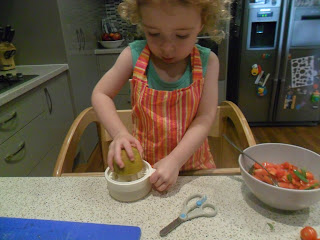 Young girl juicing half a lemon for homemade salsa