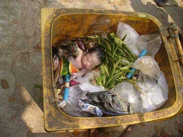 Shocking Photo of a Child Abandoned in Trash Bin