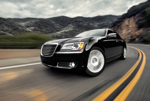 Front 3/4 view of black 2011 Chrysler 300 driving on mountain road