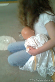girl holds doll under left arm, grasping water jug with right hand