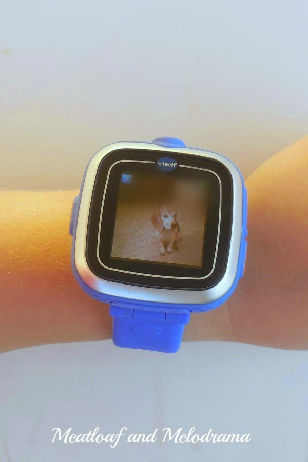 boy wearing Vtech smartwatch with picture of a beagle