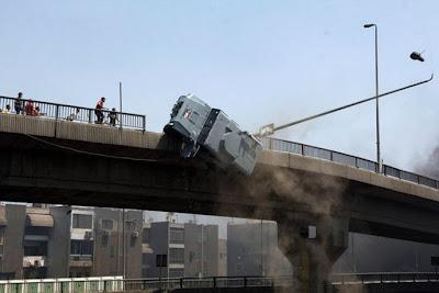 Une voiture de police est poussée hors d'un pont par des manifestant égyptiens.