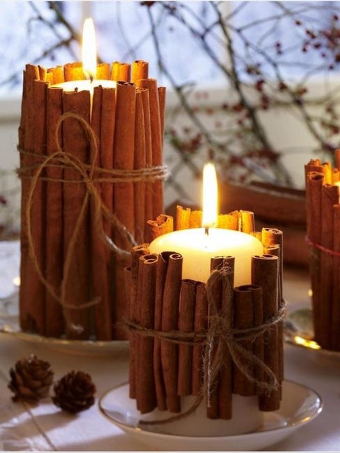 White candles with cinnamon sticks around them