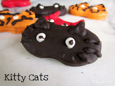 nutter butter cookies decorated to look like cat halloween masks