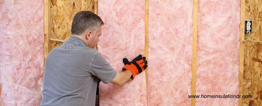 Colocación de lana de fibra de vidrio para aislar muros de madera