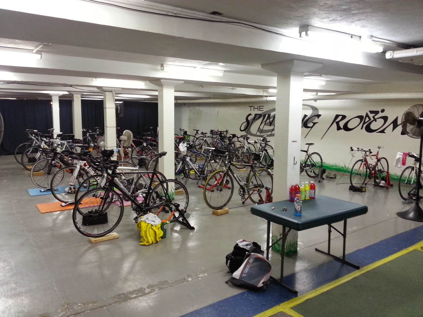 A window-less basement room with lots of bikes set up on trainers.