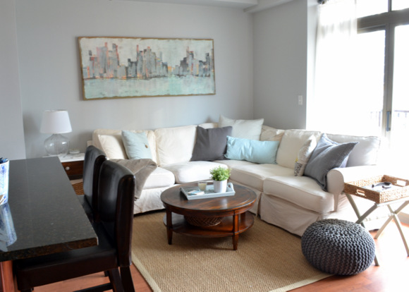 Family room with a white couch and skyline painting on the wall.