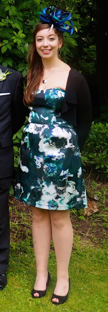 Turquoise Tranquility - wedding outfit of blue and green floral strapless dress with matching fascinator and black jacket and shoes