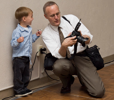 The photographer shows a picture on his camera to a gleeful young boy.