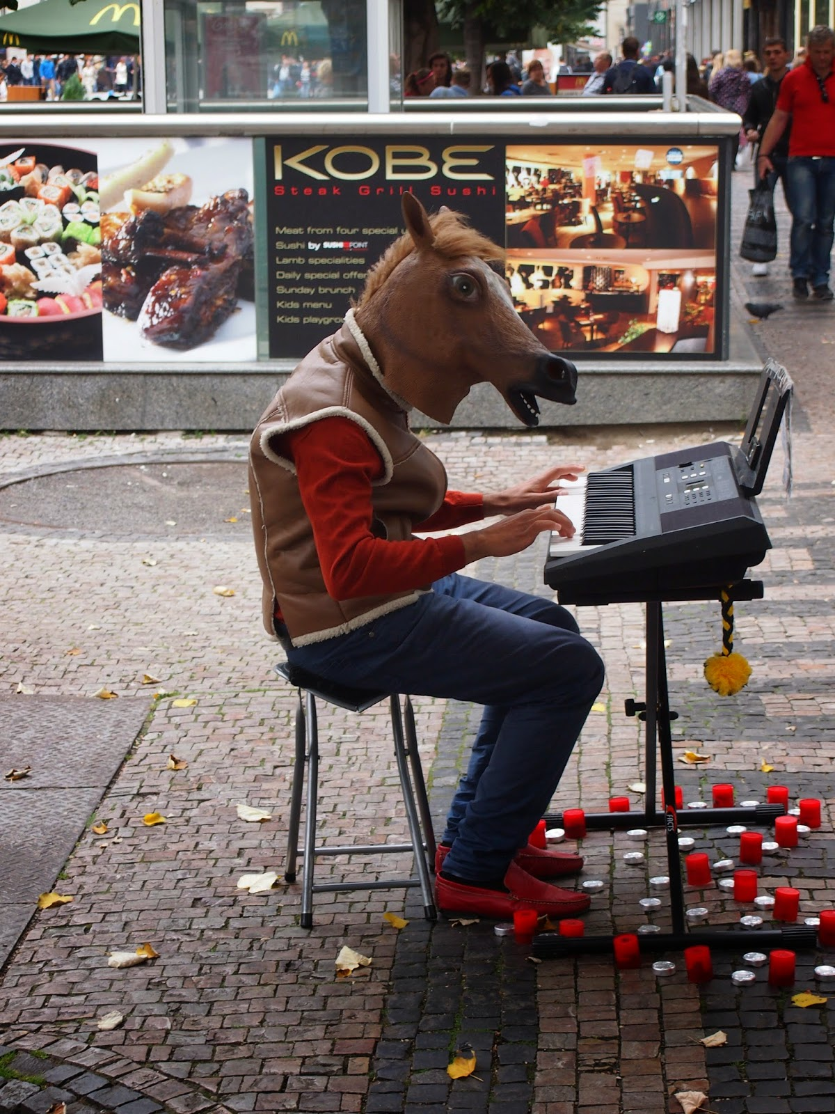 A man wearing a horse head playing a keyboard in Prague