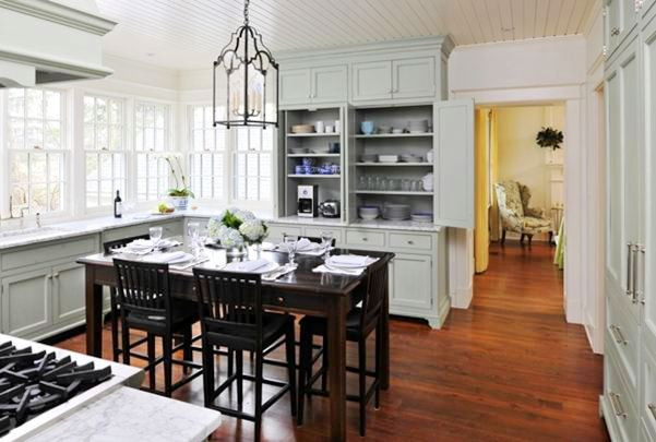 Alternative view of the kitchen and its grey cabinets, marble counter tops, casement windows, stained oak table dining room table surrounded by matching chairs and a chandelier