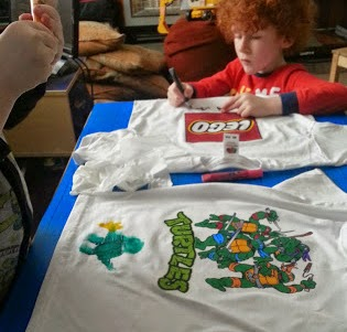 Children decorating t shirts with fabric paint pens