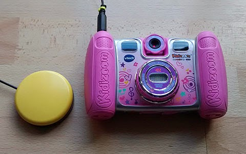 Kiddizoom Twist Plus, switch adapted for use with accessibility switch. (Pink camera and yellow switch). Front view of camera.