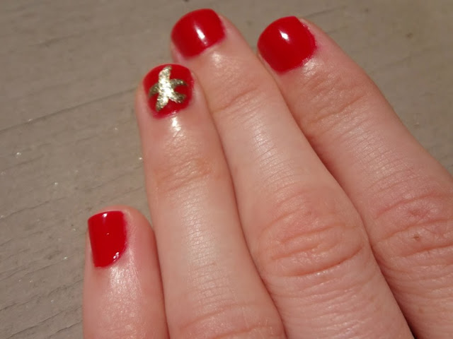Gold nail art: starfish on red nails