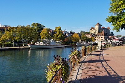 Photo of Annecy in autumn with the lake, the boats and the castle
