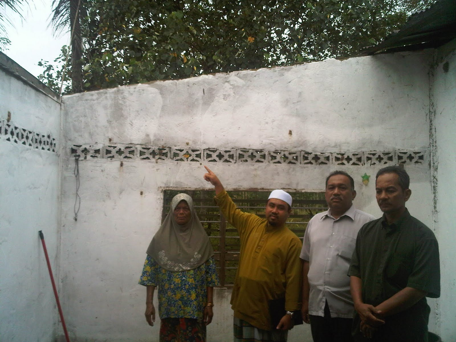YB Ustaz Mohd Nasir Zakaria menunjukan atap yang terkena ribut.Sebelah belaiu ialah isteri kepada En Ismail.Turut bersama ialah MKK Tandop Besar Sdr Omar Mad Zain ( Berbaju Hijau) Dan Pengarah Majlis Tindakan Dun Pedu saudara Shukri Abdullah.)