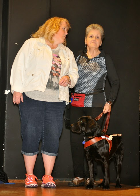 GDB puppy raising leader Kelli Reiter stands on stage with GDB graduate Marlaina Lieberg and her guide dog Nisha (black Lab)